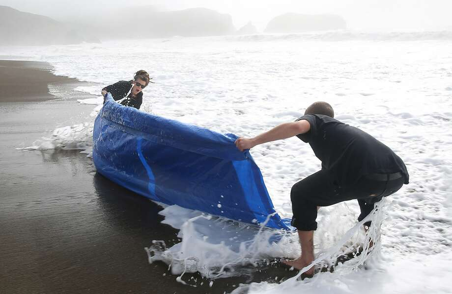 "San Francisco photographer Meghann Riepenhoff (left) works with assistant Simon Wolf on producing abstractions with ocean waves while exposing cyanotype on Strathmore Bristol paper at Rodeo Beach in Sausalito. Riepenhoff has a solo exhibition called ""Littoral Drift"" which runs at San Francisco Camerawork through Feb. 3. Photo: Liz Hafalia, The Chronicle"