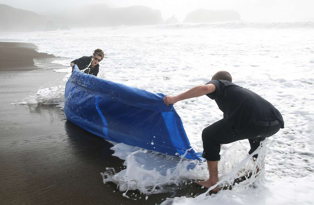 San Francisco photographer Meghann Riepenhoff (left) works with her assistant Simon Wolf (right) on producing abstractions with ocean waves while exposing cyanotype on strathmore bristol paper at Rodeo Beach in Sausalito, California, on Monday, December 7, 2015. Reipenhoff has a solo exhibition called