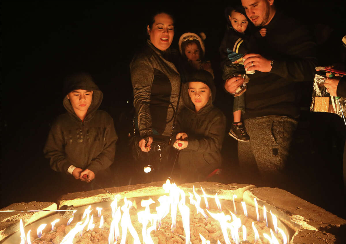Yandel Ortiz (from left), 7, Erika Ortiz holding Hanna Ortiz, 1, Nathan Ortiz, 5, and James Alamillo, holding Ethan Jase, 2, enjoy roast marshmallows for s'mores and enjoy hot chocolate following the Country Christmas Hayride during Christmas at the Caverns at Natural Bridge Caverns on Friday, Dec. 4, 2015. The holiday attraction features two underground Christmas shows: Caroling in the Caverns and Journey to Bethlehem, the AMAZEn' Reindeer Roundup, the hayride, Canopy Challenge and