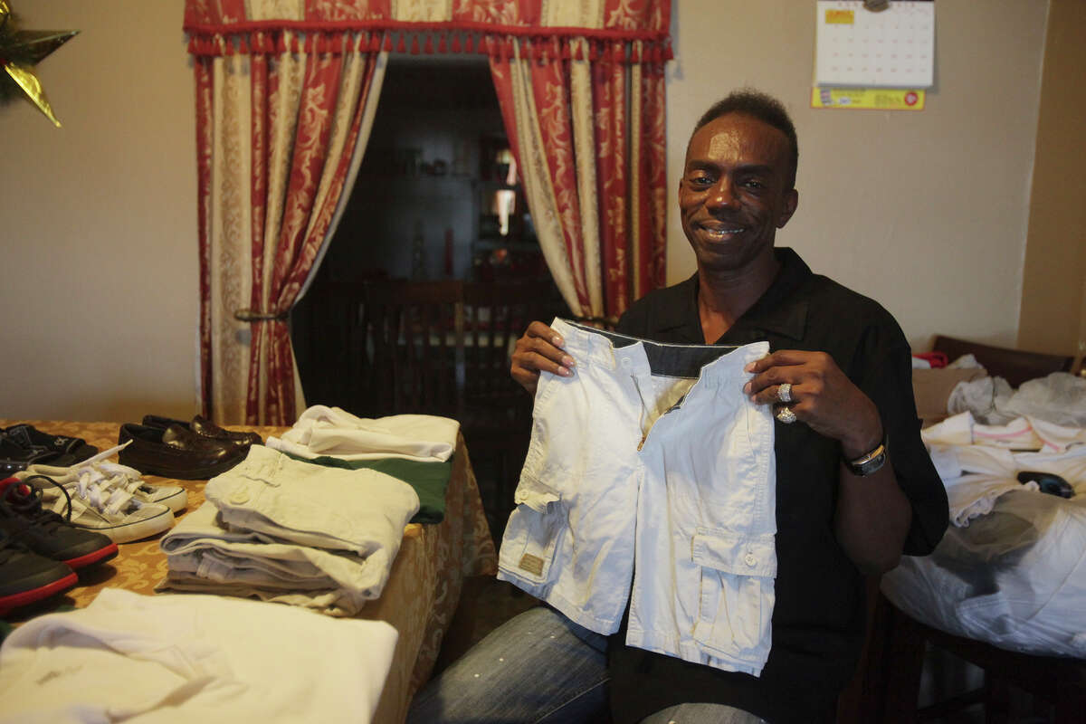 In this 2013 photo, Willie Rucker shows some of the donated clothes he has gathered for youth in need on the East Side at his home in San Antonio. He founded the non-profit Rucker Helping Kids and Youth to the Next Level to help kids through school and beyond graduation.