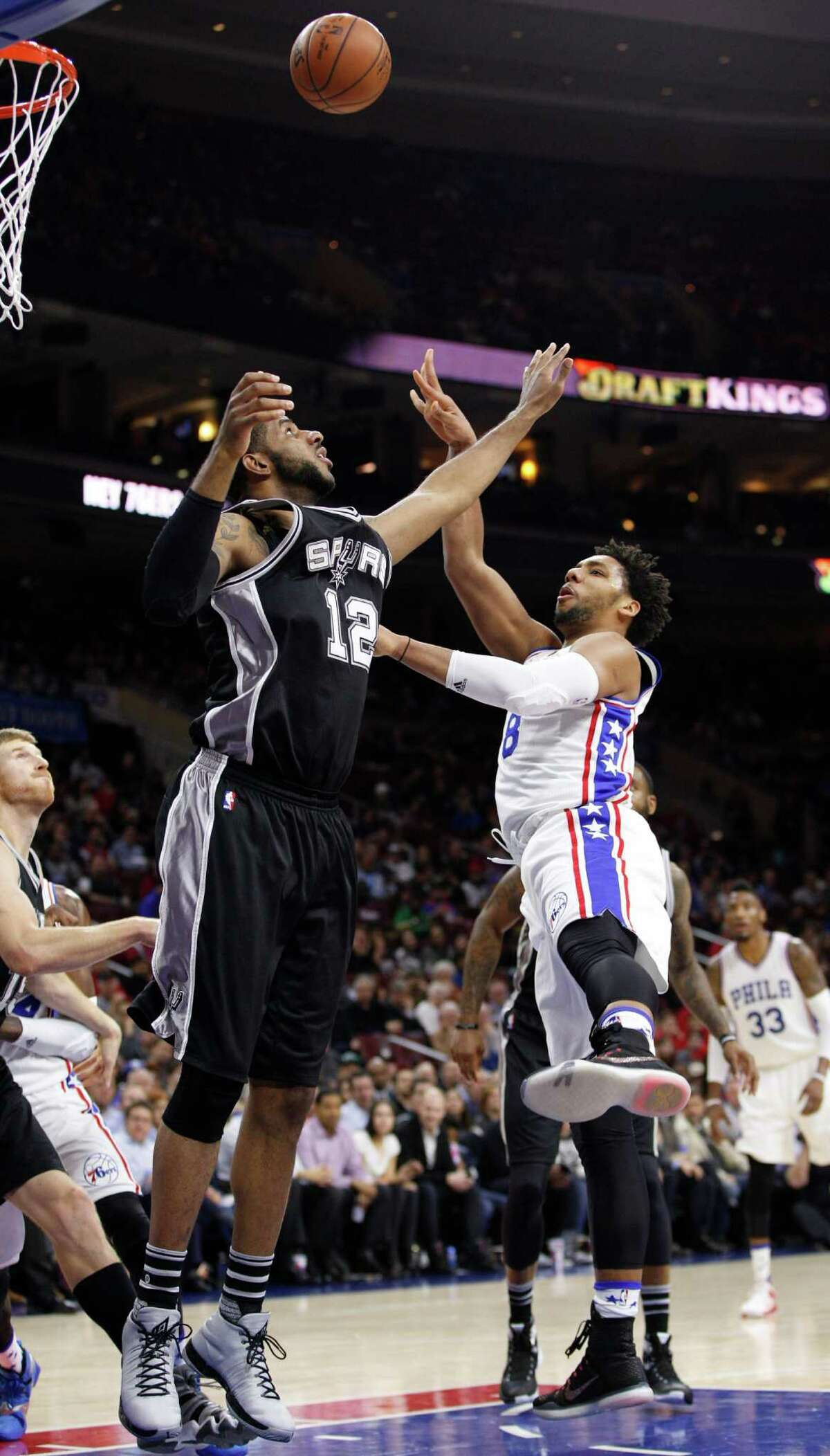 2799 x 4904~~$~~Philadelphia 76ers' Jahlil Okafor, right, puts up the shot with San Antonio Spurs' LaMarcus Aldridge, left, defending during the first half of an NBA basketball game, Monday, Dec. 7, 2015, in Philadelphia.