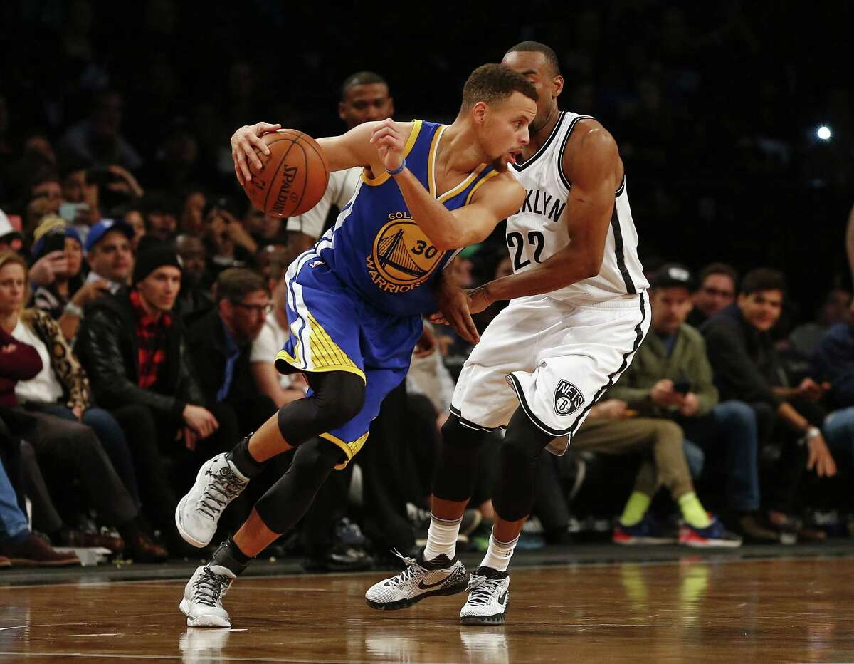 NEW YORK, NY - DECEMBER 6: Stephen Curry #30 of the Golden State Warriors attempts to get past Markel Brown #22 of the Brooklyn Nets during the fourth quarter in an NBA basketball game at the Barclays Center on December 6, 2015 in the Brooklyn borough of New York City. The Warriors defeated the Nets 114-98. NOTE TO USER: User expressly acknowledges and agrees that, by downloading and/or using this Photograph, user is consenting to the terms and conditions of the Getty Images License Agreement. (Photo by Rich Schultz/Getty Images) ORG XMIT: 575727921