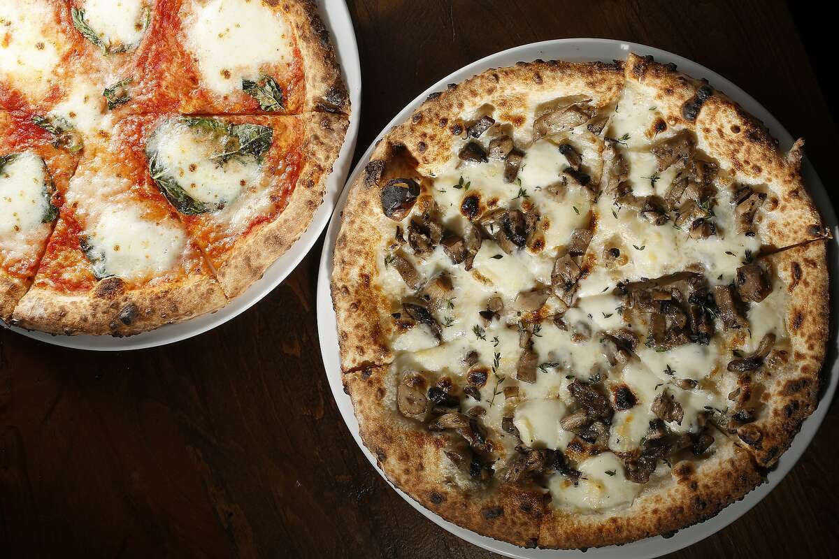 Margherita pizza (left)--house-made Fior Di Latte, basil, San Marzano tomato, olive oil--and Funghi pizza (right)--roasted local mushrooms, thyme, fontina, taleggio--are part of the menu at Caputo in San Francisco, California, on Friday, December 4, 2015.