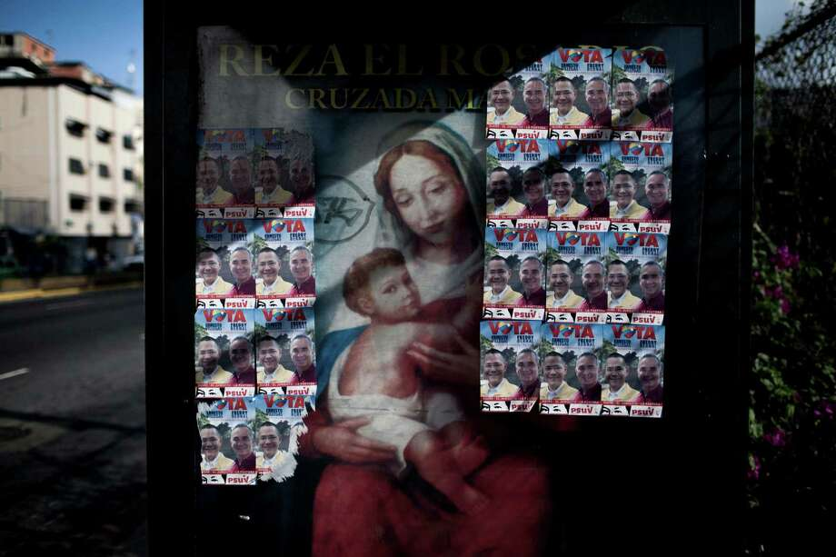 An image of the Virgin Mary, covered by political posters of pro-government congressional candidates, cover a bus stop in Caracas, Venezuela, Monday, Dec. 7, 2015, one day after congressional elections.  (AP Photo/Alejandro Cegarra) Photo: Alejandro Cegarra, STR / AP