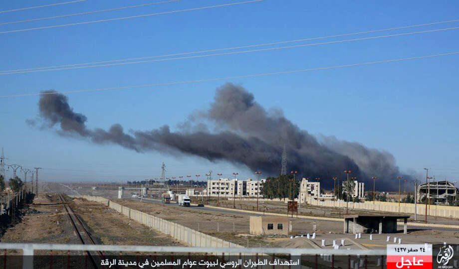 """This image posted online Sunday, Dec. 6, 2015, by supporters of the Islamic State militant group on an anonymous photo sharing website, shows smoke rising in the aftermath of an airstrike that targeted areas in Raqqa, Syria. The photo bears the watermark of Islamic State media releases and is consistent with other AP reporting. The Arabic caption on the photo reads, """"Russian warplanes target homes of Muslims in Raqqa."""" (militant photo via AP) ORG XMIT: BEI101 Photo: Uncredited / Militant photo"""