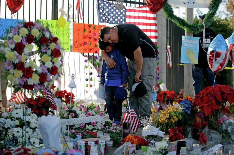 Gary  Mendoza, and his son Michael pay their respects at a makeshift memorial site honoring Wednesday's shooting victims Monday, Dec. 7, 2015, in San Bernardino, Calif. Thousands of employees of San Bernardino County are preparing to return to work Monday, five days after a county restaurant inspector and his wife opened fire on a gathering of his co-workers, killing 14 people and wounding 21.  (AP Photo/Jae C. Hong) ORG XMIT: CACC108 Photo: Jae C. Hong / AP