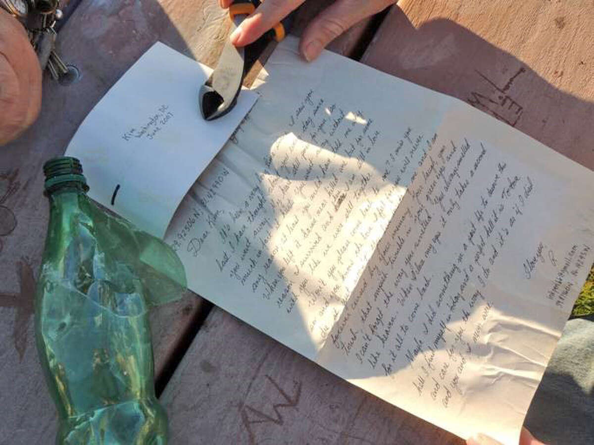 """City Rep. Kieran Ryan found a green plastic bottle with a love letter and photograph inside while helping clean up Czecik Park estuary in Stamford on Saturday. The letter is addressed to """"Kim"""" and signed """"R."""""""