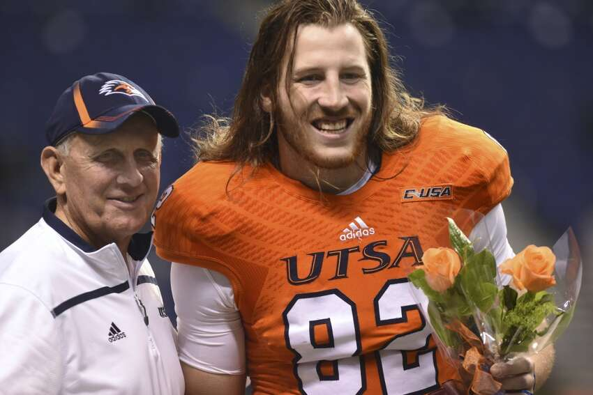 UTSA senior tight end David Morgan II carries flowers as he stands with coach Larry Coker before the team's game against Middle Tennessee State in college football action in the Alamodome on Saturday, Nov. 28, 2015.