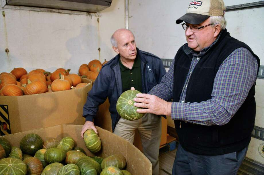 Mark Quandt, left, of the Regional Food Bank of Northeastern New York accepts a load of produce from Larry Eckhardt of Kinderhook Creek Farm as farmers from across the state kick off New York Farm Bureau's major food donations to the Regional Food Bank of Northeastern New York and the other food banks in New York State Tuesday Dec. 8, 2015 in Colonie, NY.  (John Carl D'Annibale / Times Union) Photo: John Carl D'Annibale / 10034551A