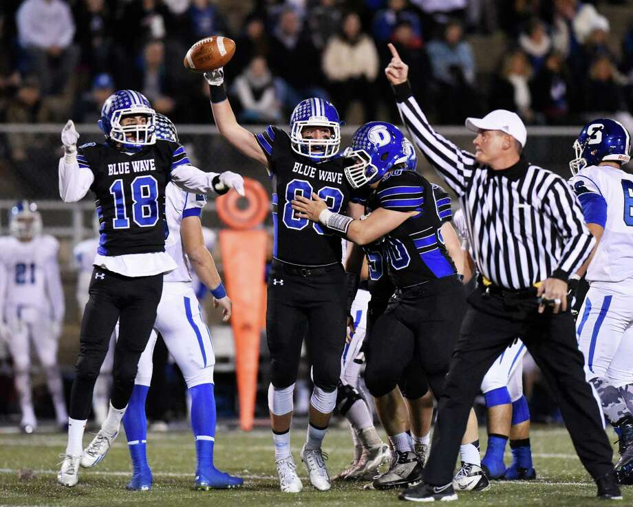 Darien's Tyler Grant (18), Quinlin Fay (83) and Mark Evanchick (90) celebrate after recovering a fumble in the opening minutes of their Class LL semifinal win over Southington Monday. Photo: Tyler Sizemore / Hearst Connecticut Media / Greenwich Time