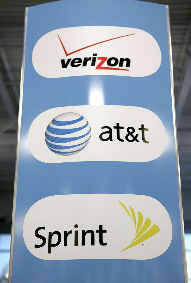 A sign for Verizon, AT&T, and Sprint mobile phones at a Best Buy store in San Francisco. A whistle-blower lawsuit alleges that Verizon, AT&T, Sprint and T-Mobile overcharged government customers. Photo: Jeff Chiu / Jeff Chiu / Associated Press / AP