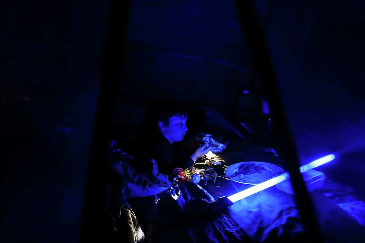 Devyn Hannahs, 6, eats dinner in his family's tent by the light of a toy lightsaber. With no electricity in the camp and dusk falling early this time of year, Devyn spends most of the evening in the dark tent, trying to keeping warm. Photo taken Nov. 12, 2015.