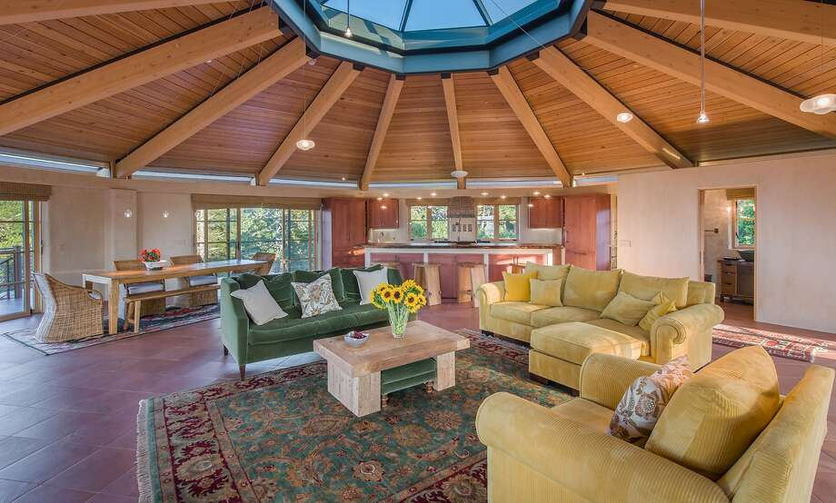A skylight forms the center of the great room's radial ceiling, while lath and plaster walls surround the tile floor.