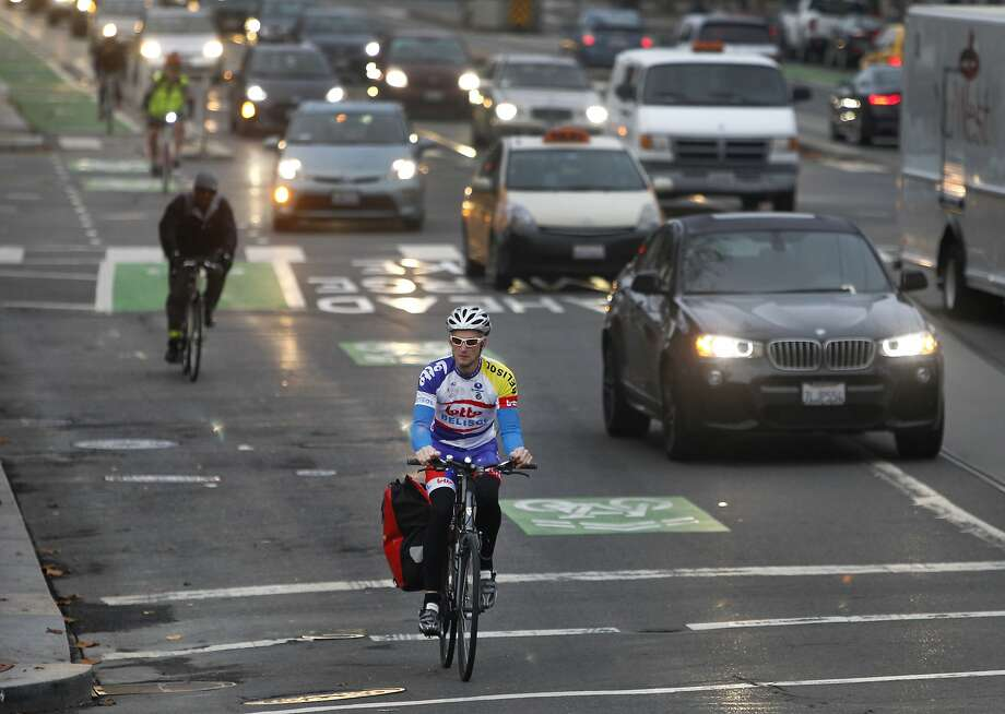 Bicyclists ride inbound on Market Street near Valencia Street in San Francisco. Supervisor John Avalos is moving forward with his proposal to permit bicyclists to roll through stop signs, a plan that Mayor Ed Lee says he would veto. Photo: Paul Chinn, The Chronicle