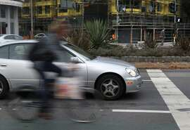 A bicyclist rides past cars stopped for a red light on Market Street near Gough Street in San Francisco, Calif. on Tuesday, Dec. 8, 2015. Supervisor John Avalos is moving forward with his proposal to permit bicyclists to roll through stop signs, a plan that Mayor Ed Lee says he would veto.