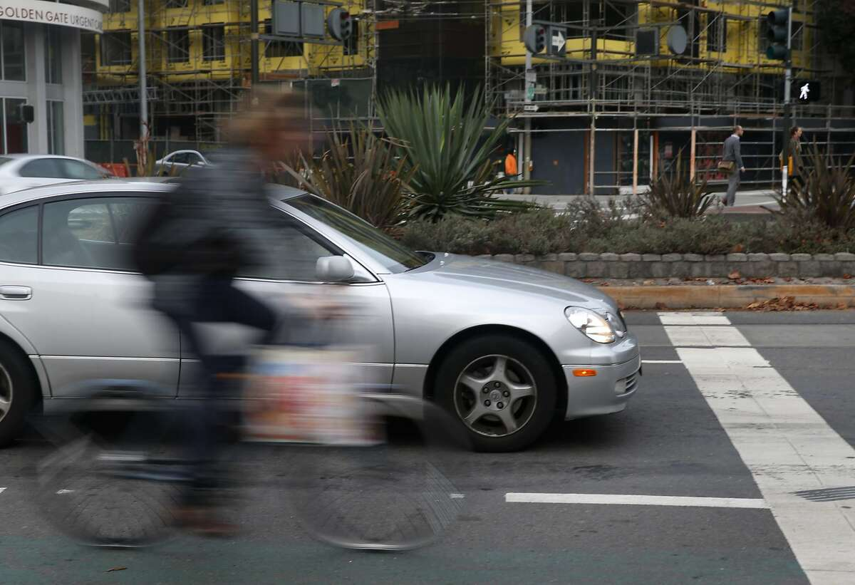 A bicyclist rides past cars stopped for a red light on Market Street near Gough Street in San Francisco. Supervisor John Avalos is moving forward with his proposal to permit bicyclists to roll through stop signs, a plan that Mayor Ed Lee says he would veto.