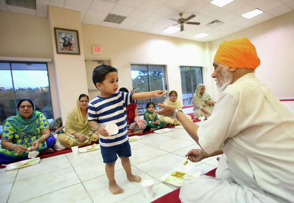 Akshveer Singh, 1, hands a piece of food to Balkar Singh, right, after an evening service last year at the Sikh Center of San Antonio. Its langer, or communal kitchen, is a symbol of equality, serving people of any religion or social class. The Sikh Center of San Antonio opened in 2001 to serve a growing Sikh community here.