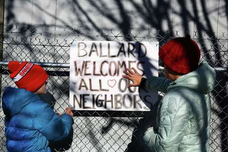 """Susan Freccia (right) and daughter Ava, 12, post a sign reading """"Ballard Welcomes All Our Neighbors"""" on the fence around the new Nickelsville site on its opening day, Nov. 21, 2015.  They live close by and wanted to show their support for the camp. Photo: GENNA MARTIN, SEATTLEPI.COM / SEATTLEPI.COM"""