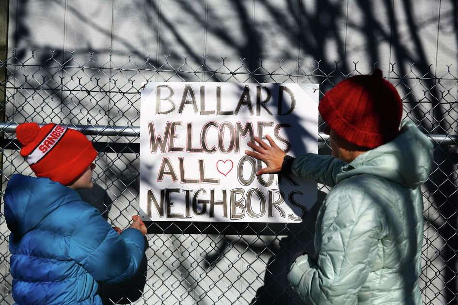 "Susan Freccia (right) and daughter Ava, 12, post a sign reading ""Ballard Welcomes All Our Neighbors"" on the fence around the new Nickelsville site on its opening day, Nov. 21, 2015.  They live close by and wanted to show their support for the camp."