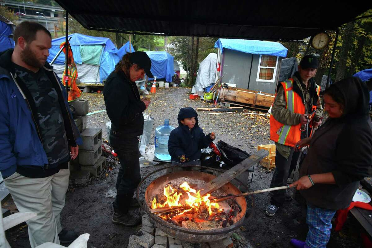 Residents of Nickelsville Dearborn gather around the fire pit to keep warm, Nov. 16, 2015.