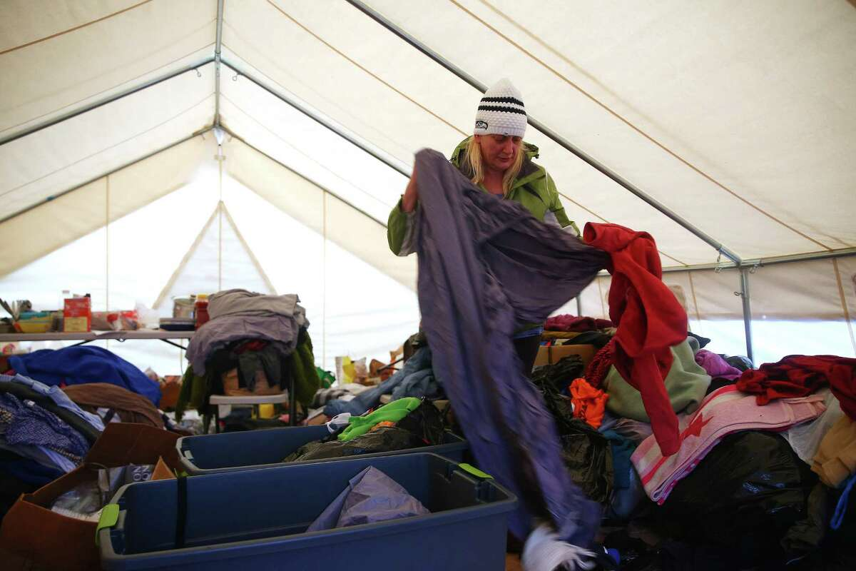 Danielle Romo sorts through donations three days after moving into Nickelsville Ballard. She has been homeless for about a year after being evicted from her apartment when a new owner bought the building and no longer wanted to provide Section 8 housing. The three newly authorized camps would be similarly run to this camp.