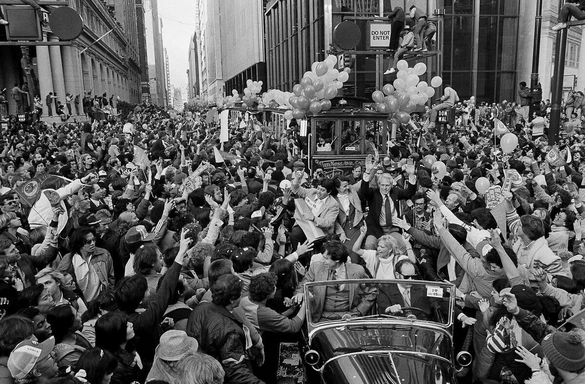 Forty-Niners coach Bill Walsh, right, rides with team owner Eddie DeBartolo and Mayor Dianne Feinstein down San Francisco's Market Street, Jan. 25, 1982. Huge crowds greeted the team that gave the city its first world championship in a major sport with their Super Bowl win Sunday.