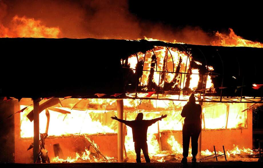 Protesters take their pictures in front of a building set afire in Ferguson, Mo., after the 2014 shooting of Michael Brown by a police officer.  Photo: Robert Cohen, MBI / St. Louis Post-Dispatch