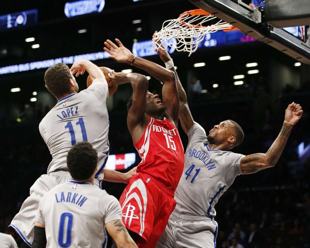 Brooklyn Nets center Brook Lopez (11) and Nets forward Thomas Robinson (41) knock the ball from Houston Rockets center Clint Capela (15) in the first half of an NBA basketball game, Tuesday, Dec. 8, 2015, in New York. (AP Photo/Kathy Willens)