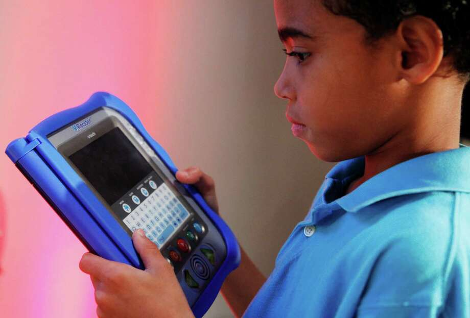 Children using devices such as VTech's V.Reader may have had their personal data stolen after VTech's database was breached.  Photo: Mark Lennihan, STF / AP