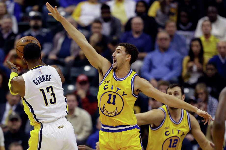 The Warriors' Klay Thompson, right, adds a bit of defense on Paul George to the mix on a night when he scored 39 points before leaving with a sprained ankle. Photo: Michael Conroy, STF / AP