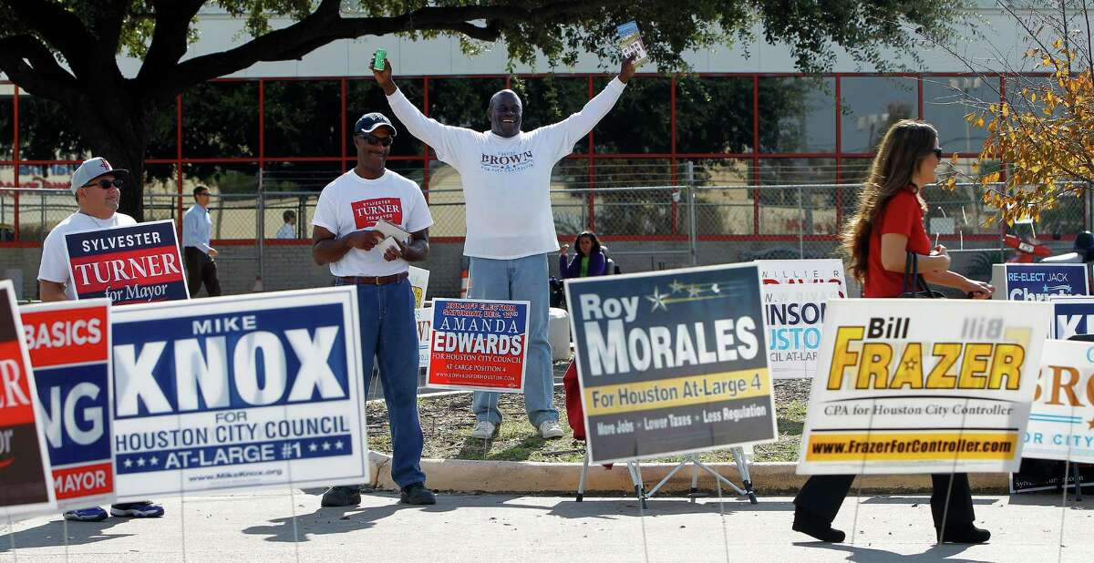 Michael Holmes, waves at a voter alosnt with Edward Zaragoza, and Lawrence Bell, who were handing out fliers for their candidates outside of the Metropolitan Multi-Service Center, 1475 W. Gray Street, during the last day of early voting in Harris County on Tuesday, Dec. 8, 2015, in Houston .