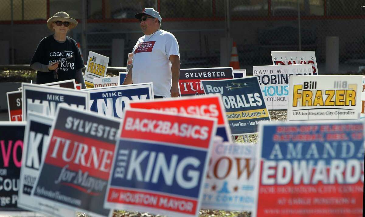 Patricia Rayburn, left, and Edward Zaragoza hand out fliers for their candidates outside of the Metropolitan Multi-Service Center, 1475 W. Gray Street, during the last day of early voting in Harris County on Tuesday, Dec. 8, 2015, in Houston .