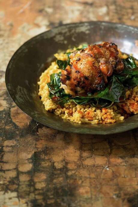 """Chicken Thighs with Red Palm-Coconut Rice from """"Senegal: Modern Senegalese Recipes from the Source to the Bowl"""" by Pierre Thiam with Jennifer Sit (Lake Isle Press, $35). Photo: Lake Isle Press"""