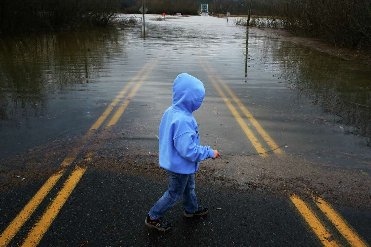 Five-year-old Bryce Carlson, of Carnation, checks out the waterline on the flooded NE 124th Street outside of Duvall, Wednesday, Dec. 9, 2015. The Snoqualmie River reached severe flood levels late Tuesday.