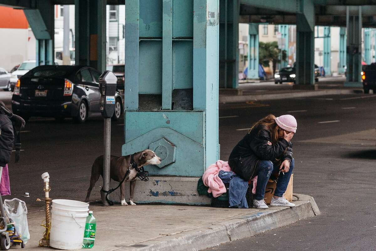 A woman holds her head in her hands while waiting for a friend to arrive under the 101 offramp at Division and Folsom Streets in San Francisco, Calif., Wednesday, December 9, 2015.