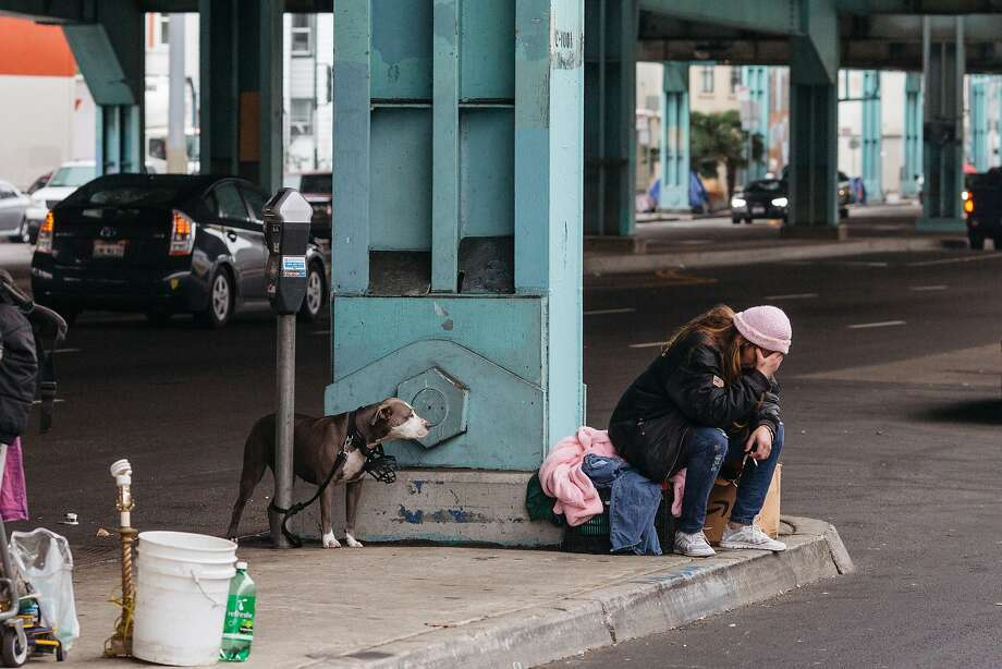 Above: A woman holds her head in her hands while waiting for a friend to arrive under the 101 offramp at Division and Folsom Streets in San Francisco, Calif., Wednesday, December 9, 2015. Photo: Jason Henry, Special To The Chronicle