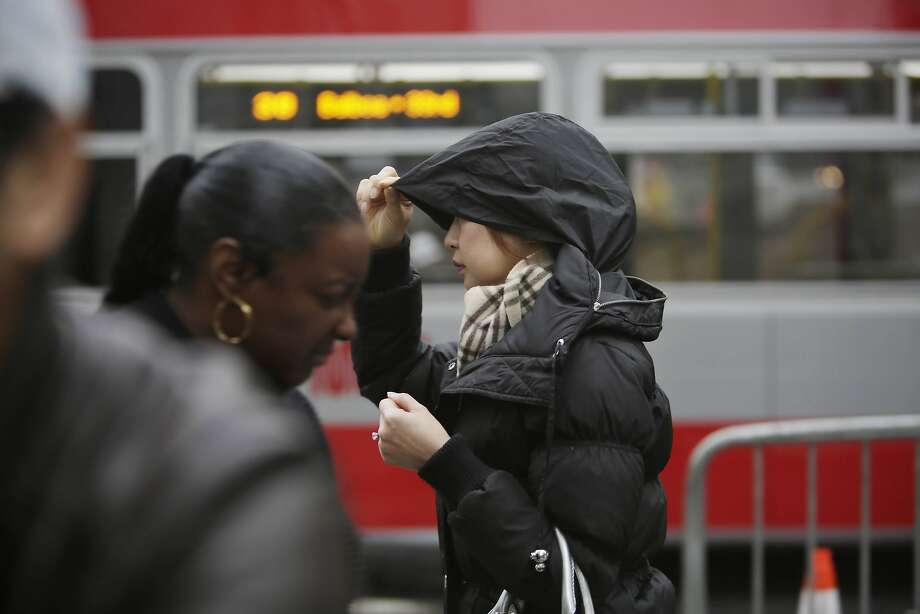 Kamonpun Loima of San Francisco, pulls her hood securely over her head during a light rain while running errands as she walks along Geary Street on Dec. 9, 2015 in San Francisco. A series of storms is poised to bring rain to the Bay Area and snow to the Sierra beginning on Friday. Photo: Lea Suzuki, The Chronicle