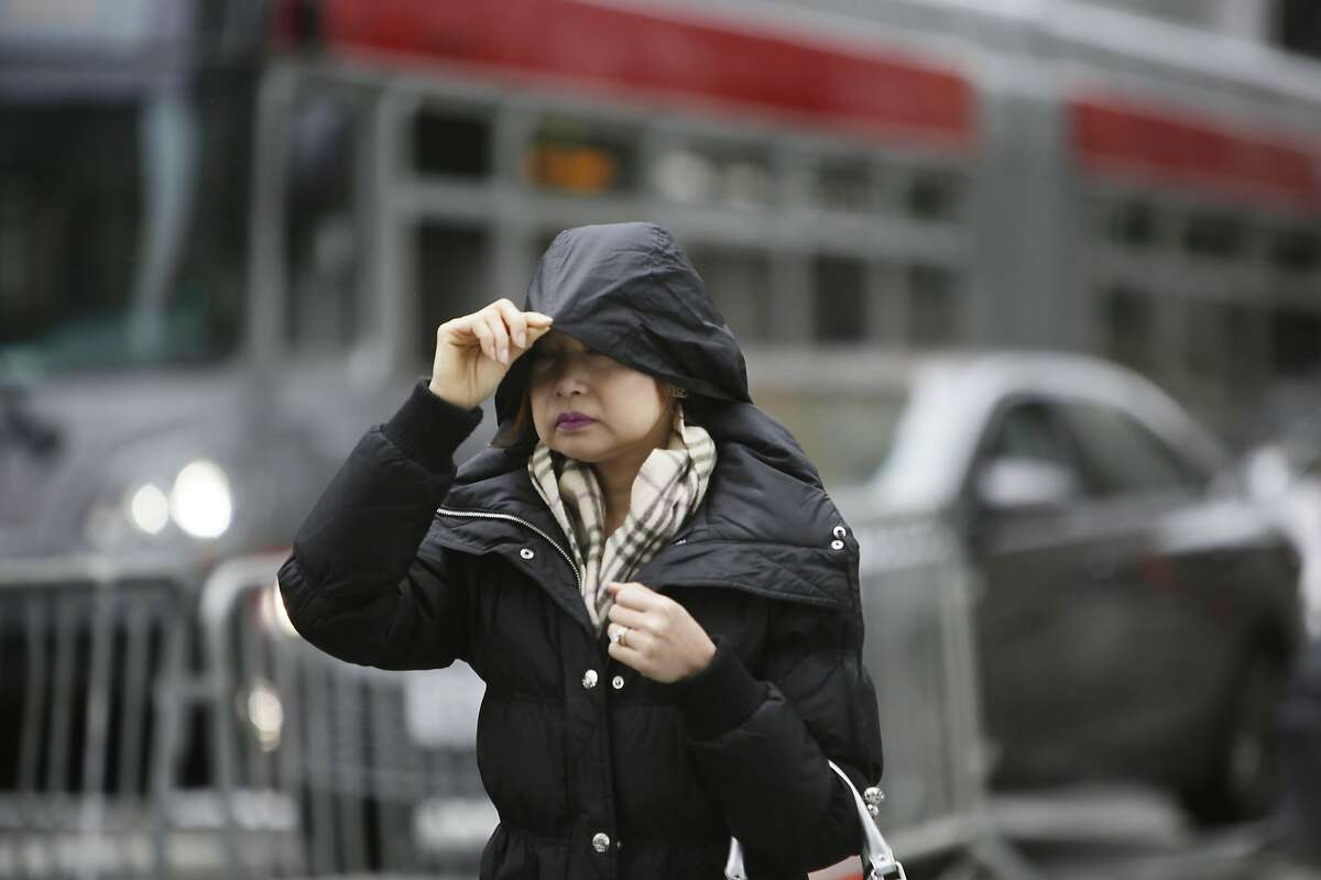 Kamonpun Loima of San Francisco, pulls her hood securely over her head during a light rain while running errands as she walks along Geary Street on Wednesday, December 9, 2015 in San Francisco, Calif.