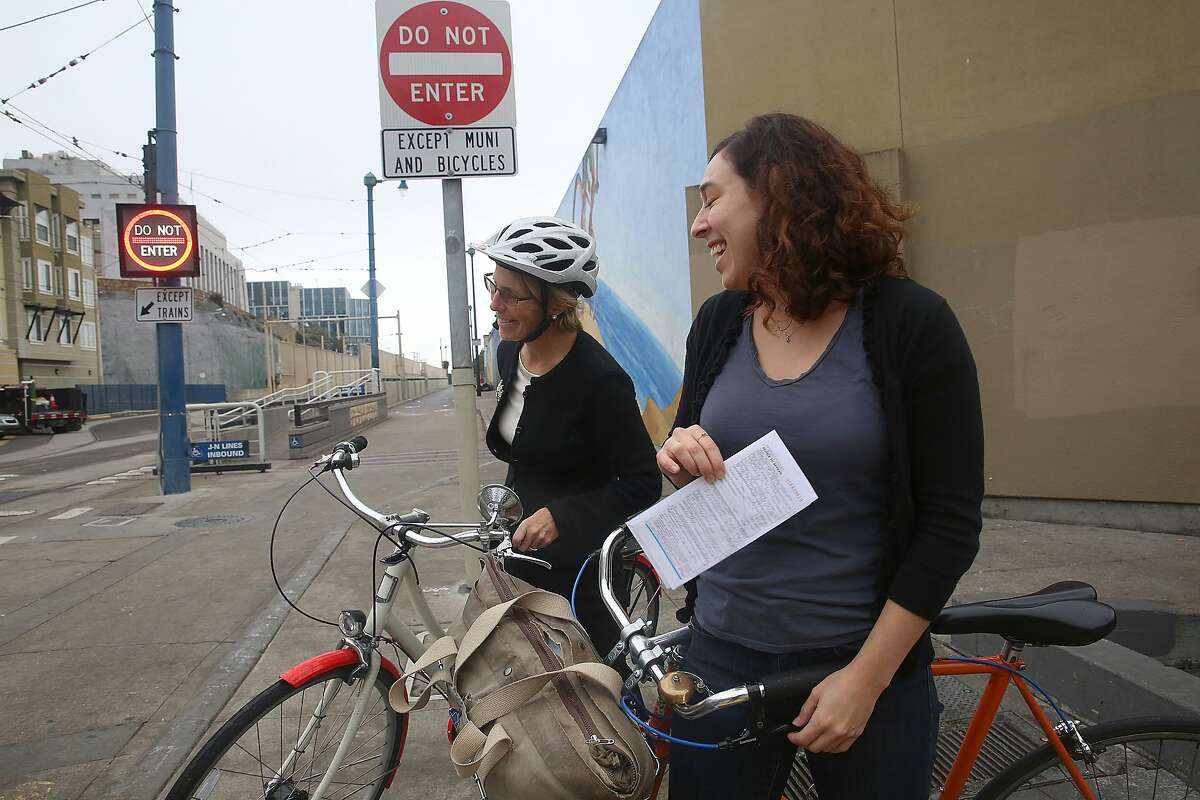 Jean Fraser (left) from San Francisco stops to talk with Katrina Sostek (right) about a ticket received for not stopping at a stop sign on Duboce at Church streets in San Francisco, California, on Tuesday, Dec. 9, 2015.