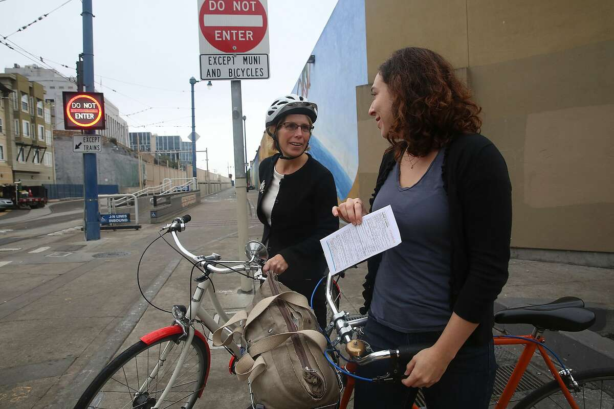 Jean Fraser (middle left) from San Francisco stops to talk with Katrina Sostek (right) about a ticket received for not stopping at a stop sign on Duboce at Church streets in San Francisco, California. Fraser says it gives her second thoughts on her cycling budget for transportation.