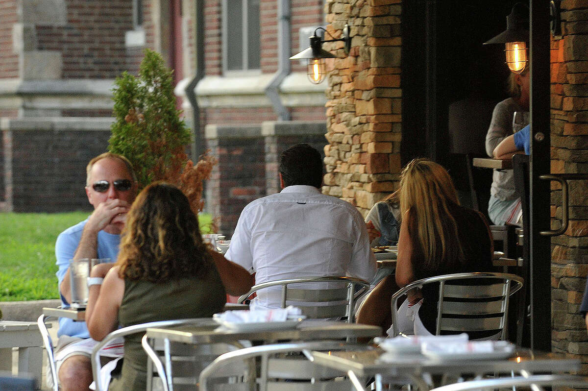Patrons sit outside Bar Rosso in downtown Stamford in August. Restaurants that offer outdoor dining will now have to pay an annual $250 fee to the city, whether the dining area is on private or public property. Establishments with tables on public property have to pay $2 a square foot on top of the fee.