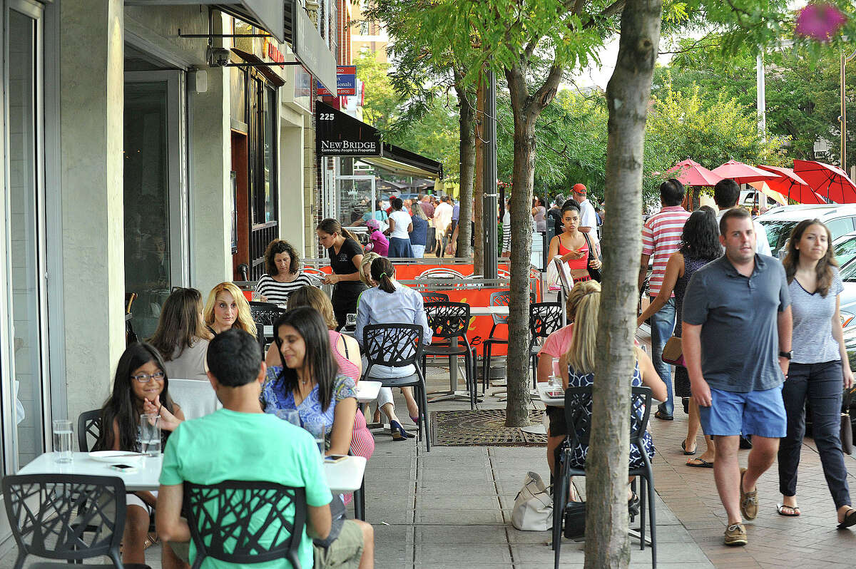 Patrons sit outside various restaurants along Bedford Street in downtown Stamford in August.Restaurants that offer outdoor dining will now have to pay an annual $250 fee to the city, whether the dining area is on private or public property. Establishments with tables on public property have to pay $2 a square foot on top of the fee.