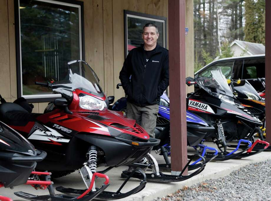 Rick Swift of Village Motorsports, poses with snowmobiles at his business on Tuesday, Dec. 8, 2015, in Speculator, N.Y. Some Northeasterners are beginning to wonder if a white Christmas may just be a dream, and business owners who rely on snow are starting to worry if warm weather could lead to a nightmare winter. (AP Photo/Mike Groll) Photo: Mike Groll, STF / AP