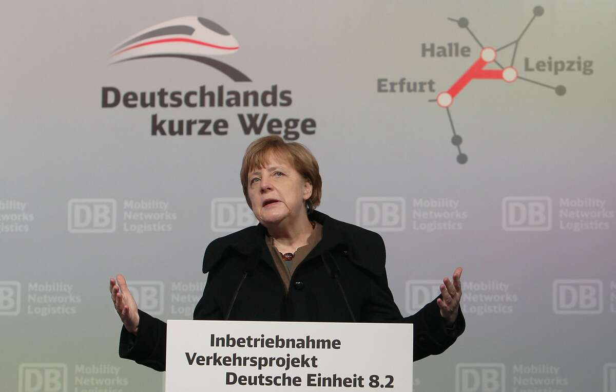 """German Chancellor Angela Merkel delivers a speech during the opening ceremony of the new high-speed rail line between Erfurt and Halle/Leipzig at the central station in Leipzig, Germany, Wednesday, Dec. 9, 2015. Letters in the background read: """"Germany's short ways"""". (Sebastian Willnow/dpa via AP)"""