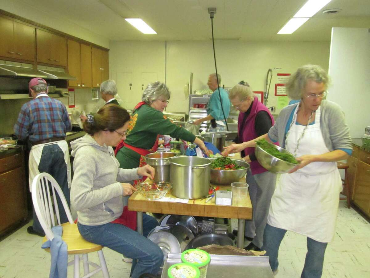 Ellie von Wellsheim, in apron at right, and other volunteers prepare meals in 2014 for the annual Dining for Dollars fundraiser. The effort this year is making cookies and quick breads instead of lasagna. (Provided photo.)
