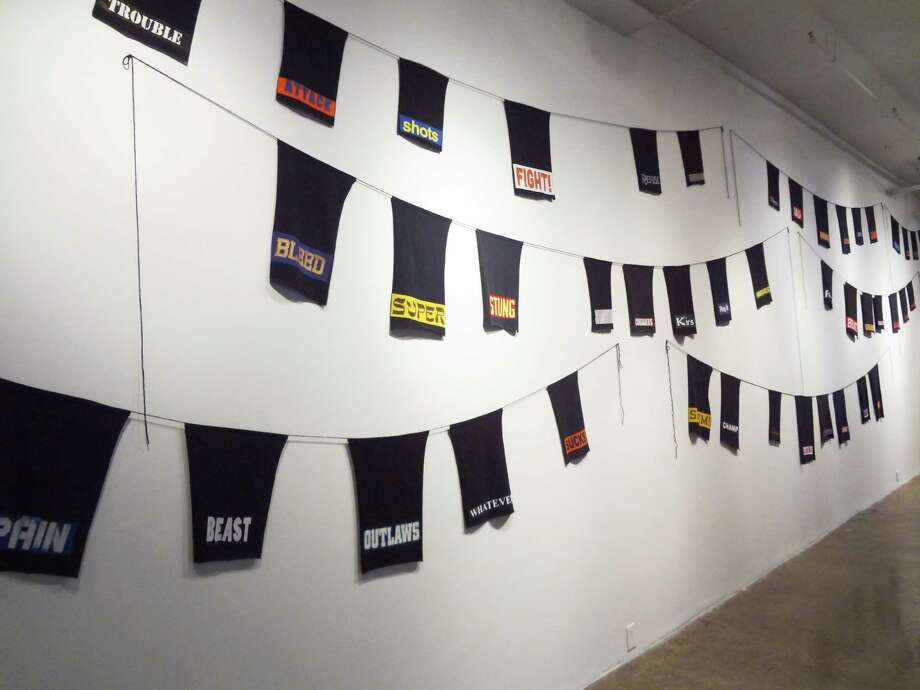 """what you say what you say what"" is an installation by San Antonio artist Charlie Morris made of found t-shirts with evocative words printed on them, recontextualized and juxtaposed to create new meanings. ""The constant barrage of commercially produced text builds shared, emotionally conditioned responses,"" he said. Photo: Courtesy Blue Star / Courtesy Blue Star"
