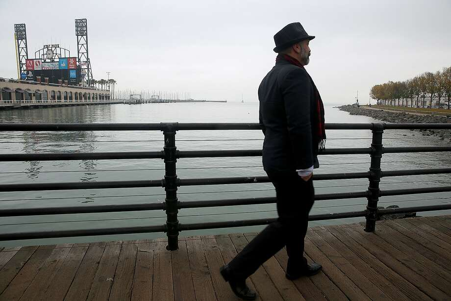 Real estate agent Donald Dewsnup walks across the Lefty O'Doul bridge while showing Mission Creek Marina at top right, and shows plans  for it's expansion of public open space in San Francisco, California, on Wednesday, December 9, 2015. Photo: Liz Hafalia, The Chronicle