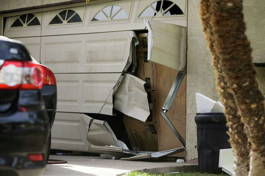 A garage door of Enrique Marquez's home is seen broken in a recent FBI raid, Wednesday, Dec. 9, 2015, in Riverside, Calif. Authorities have said Enrique Marquez, an old friend of San Bernardino attacker Syed Farook, purchased two assault rifles used in last week's fatal shooting that killed 14 people. (AP Photo/Jae C. Hong) Photo: Jae C. Hong, STF / Associated Press / AP