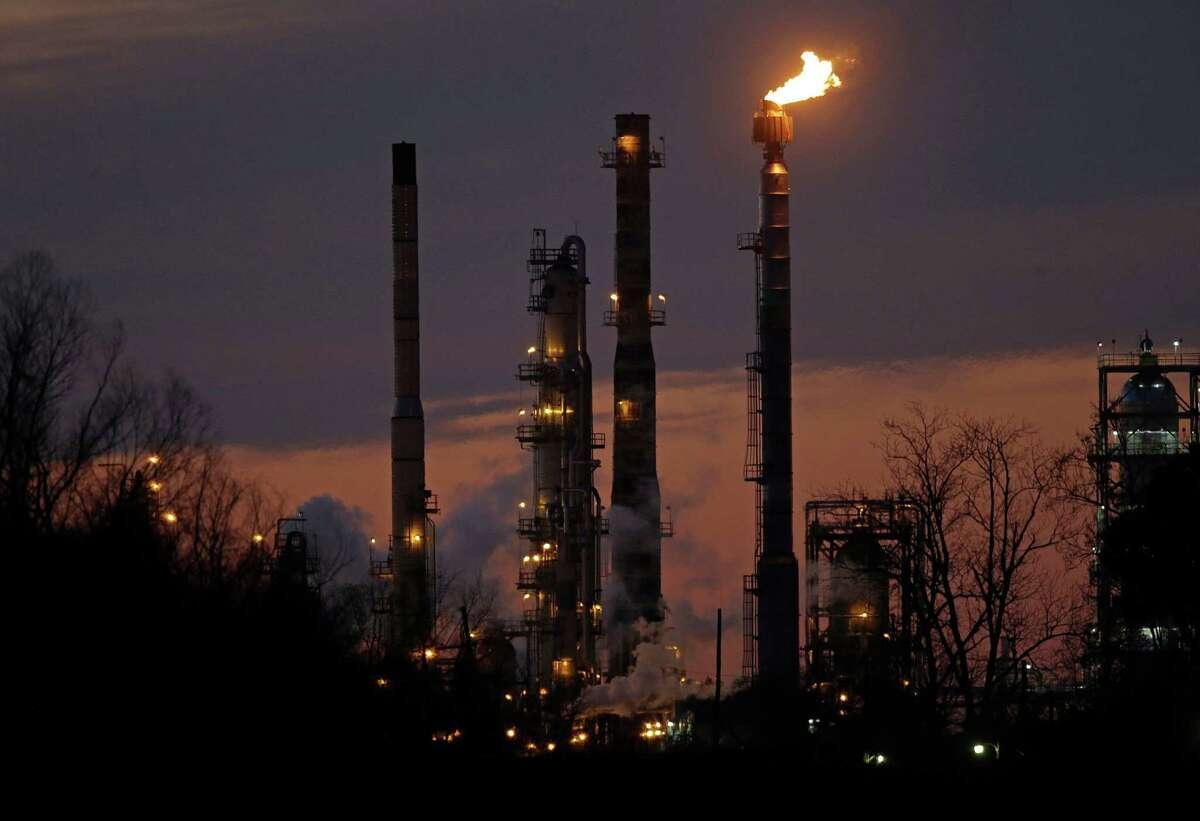 Stacks and burn-off from the Exxon Mobil refinery are seen at dusk in St. Bernard Parish, La. (AP Photo/Gerald Herbert, File)