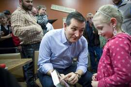 FILE-- Republican presidential hopeful  Sen. Ted Cruz (R-Texas) shows a photo of his daughters on the back of his book to Sally Vandall, 5, after speaking at a campaign event in Newton, Iowa, Nov. 29, 2015. Cruz has vaulted into the top tier of the Republican race as the consummate Washington bomb thrower, but now he is taking an almost academic approach to achieving likability. (Scott Morgan/The New York Times)